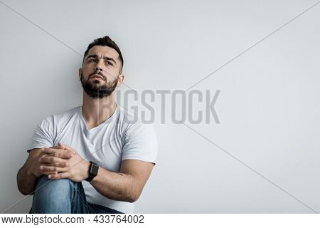 Depressed Guilty Man Sitting Against White Wall At Home Feeling Unhappy, Lonely And Sad, Depression