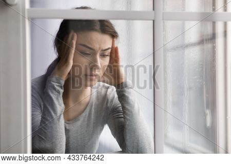 Upset Female Suffering From Health Problems, Depression And Headache, Near Window With Drops
