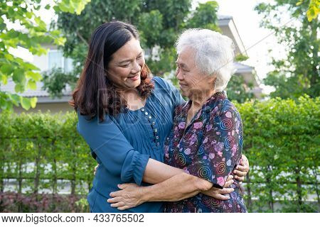 Asian Elderly Woman With Caregiver Walking Help With Love And Happy In Nature Park.