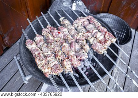 Russian Shashlik With Skewers On A Round Grill.