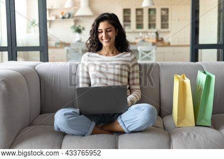 Online Shopping. Young Woman With Laptop And Shopper Bags Ordering Goods On Web While Sitting On Cou
