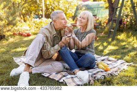 Romantic Elderly Couple Having Picnic In Their Garden, Sitting On Blanket And Eating Toasts, Spendin