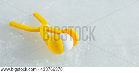 A Children's Yellow Toy-a Tool For Modeling Snowballs Lies On The Ice On A Sunny Winter Day. Tongs F