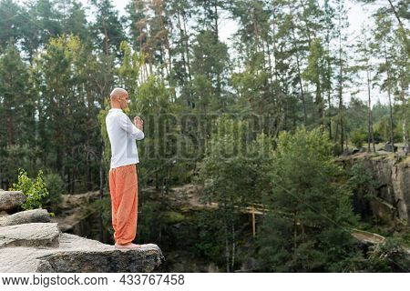 Full Length View Of Buddhist In White Sweatshirt And Harem Pants Meditating With Praying Hands On Ro