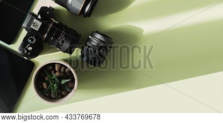 Photographers Or Videographer Equipment, Composition Of A Camera And Lenses On A Green Background, F