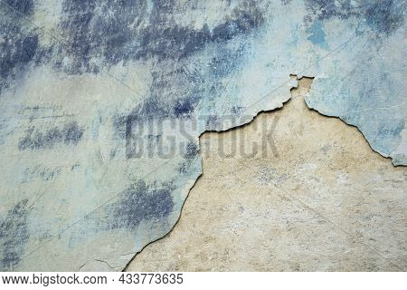Wall Of Old Building With Partially Fallen Off Plaster In Gray And Blue Colors. Space Is Divided Int