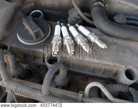 New car spark plugs on engine background