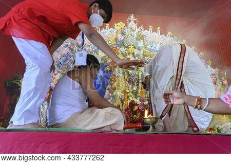 Howrah, West Bengal, India - 25th October 2020 : Masked Volunteer Boy Guiding Hindu Devotees During