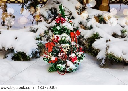 Christmas Tree, Decorated With Garlands And Toys In The Fresh Air In The Park In Winter Under Snow.