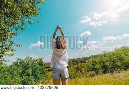 A Girl In A White Shirt And Denim Shorts Stands With Her Back And With Her Hands Up. Rural Landscape