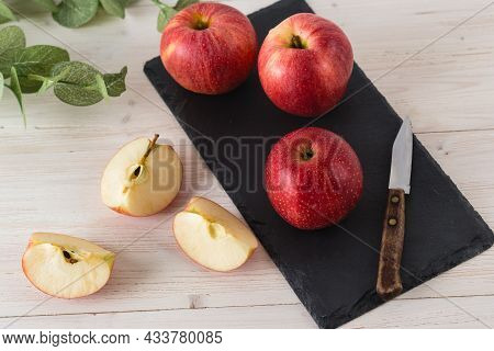 In A Rectangular Black Slate Dish On A White Wooden Table Are Three Juicy Beautiful Ripe Red Apples