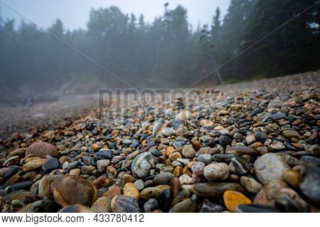 Multi-colored Round Rocks On Little Hunters Beach In Acadia National Park, Maine. Tide Coming In As