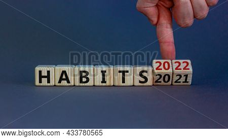 2022 Habits And New Year Symbol. Businessman Turns Wooden Cubes And Changes Words 'habits 2021' To '