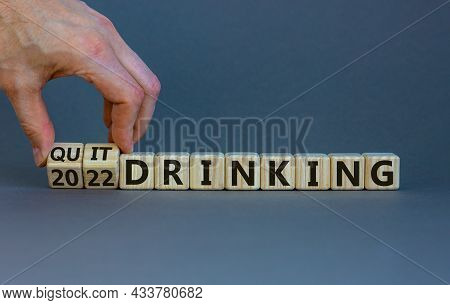 Quit Drinking 2022 New Years Resolution Symbol. Businessman Turns Wooden Cubes With Words '2022 Quit