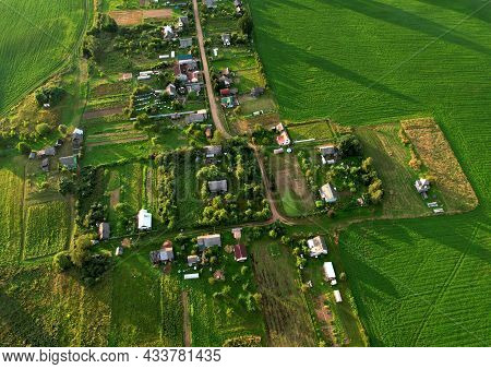 Top View Of The Village With Wooden Houses In Wild Among The Forest And Field. Aerial View Of Countr