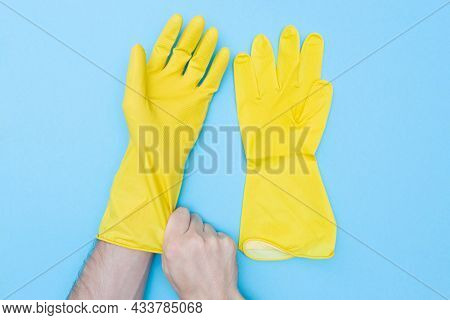 Man Puts On Protective Rubber Gloves. Yellow Gloves For Cleaning. Hand And Skin Protection. On A Blu
