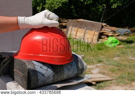 Part Of A Builders Hand And A Safety Helmet At A Construction Site.