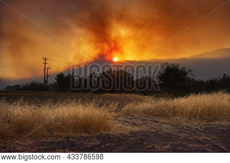 Rural Cyprus Landscape At Sunset With Agricultural Field And Dramatic Wildfire On Background