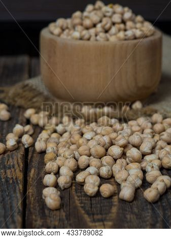 Wooden Bowl And Wooden Spoon Full Of Chickpeas On Wooden Background. Top View.chickpea