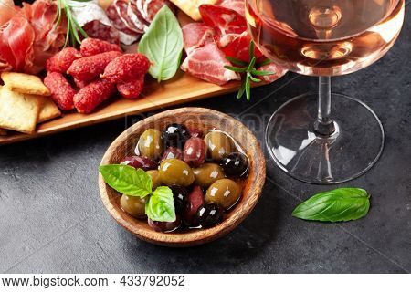 Antipasto board with prosciutto, salami, crackers, cheese, nuts, olives and rose wine