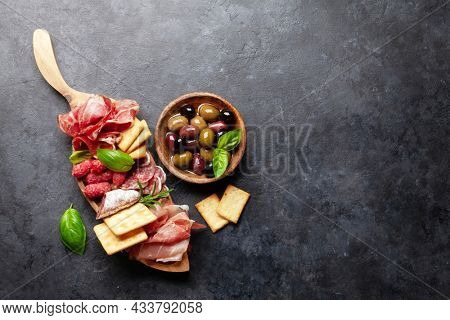 Antipasto board with prosciutto, salami, crackers and olives. Top view flat lay with copy space
