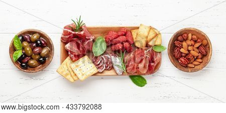 Antipasto board with prosciutto, salami, crackers, cheese, nuts and olives. Top view flat lay