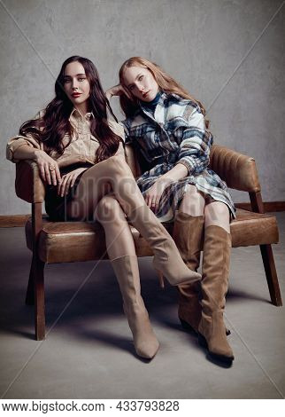 Retro Fashion: Two Beautiful Young Women Sit On Chair. Vintage Portrait Of Gorgeous Girls In Seventi