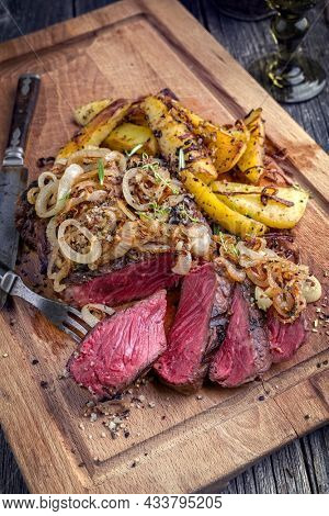 Traditional barbecue wagyu rib eye beef steak very rare and sliced with fried onions and potatoes offered as close-up on a rustic wooden board