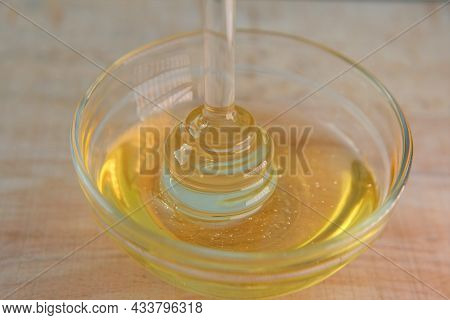 Honey. Liquid Honey In Glass Jar With Dipper.glass Stick For Honey In A Glass Cup On A Wooden Table.