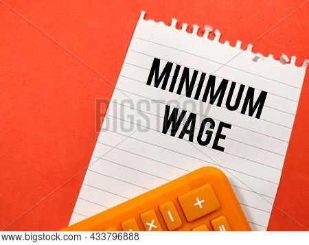 Business Concept.text Minimum Wage Writing On Notepaper With Calculator On Red Background.
