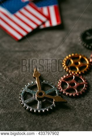 high angle view of some cogwheels, some clock hands and some small flags of the Uniteds States of America on a dark gray background