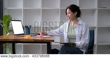 Young Undergraduate Student Studying Online Class By Laptop Computer.
