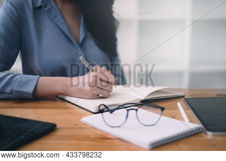 Young Undergraduate Student Studying Online Class By Laptop Computer And Taking Note