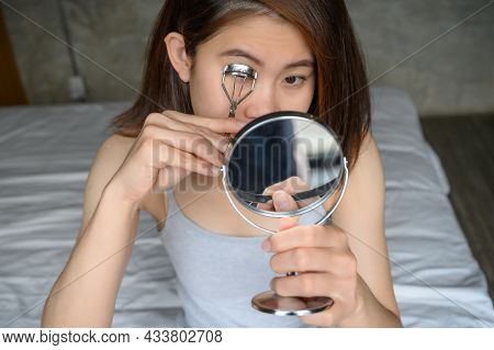 Portrait Of Young Asian Woman Using Eyelash Curler For Curling Eyelashes By Looking Mirror. Eyelash