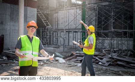 Architect, Engineer, Contractor, Or Construction Manager Holding Blueprint Standing With A Group At