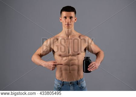 Supplements Worth Taking. Shirtless Man Point Finger At Protein Bottle. Dietary Supplements