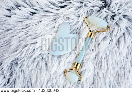 Opal Crystal Facial Roller And Massage Tool Jade Gua Sha On Grey Artificial Fur Background. Facial A