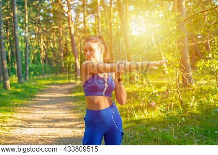 Woman Runner Stretching Arms Before Exercising In A Summer Park Morning.young Athletic Female Warmin