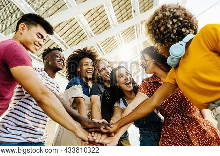 Multiracial Happy Friends With Hands In Stack. Multi-ethnic Diverse Group Of College Students Joinin
