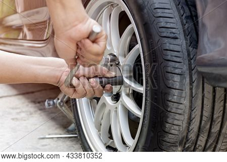 Home Service Car Concept : A Man Repairing Action Lock Bolt Of Car Wheel For Check The Car's Drive S