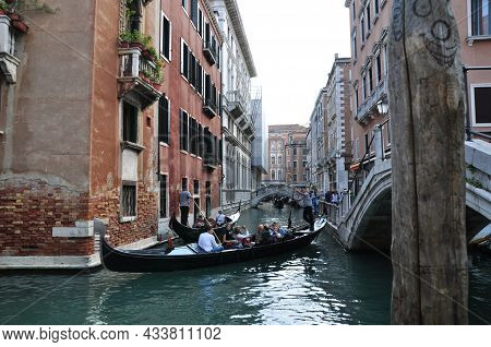 View Of One Of The Many Canals In Venice. Tourists Sail On Gondolas Along The Canal. October 12, 201