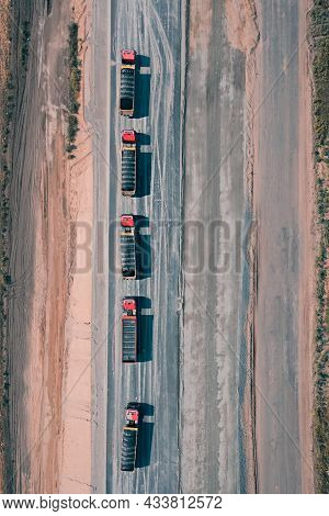 Five Trucks With Cargo Are Driving Along An Asphalt Road In The Middle Of Desert. Aerial Drone Shot.