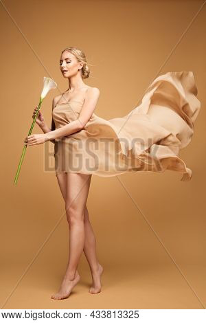 Woman Body Beauty. Slim Fit Model In Beige Waving Chiffon Dress. Graceful Girl Dancing With Calla Li