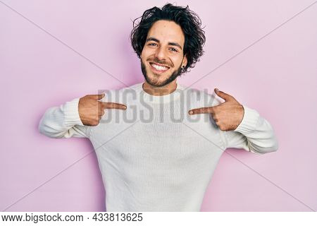 Handsome hispanic man wearing casual white sweater looking confident with smile on face, pointing oneself with fingers proud and happy.