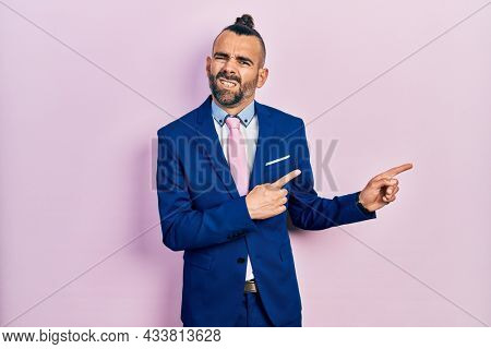 Young hispanic man wearing business suit and tie pointing aside worried and nervous with both hands, concerned and surprised expression