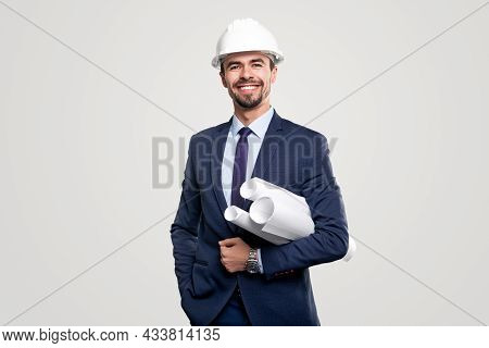 Happy Confident Bearded Male Construction Engineer In Classy Suit And Hardhat Holding Rolled Drafts