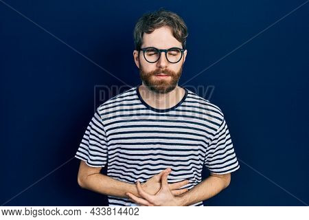 Caucasian man with beard wearing striped t shirt and glasses with hand on stomach because indigestion, painful illness feeling unwell. ache concept.