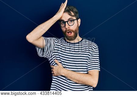 Caucasian man with beard wearing striped t shirt and glasses surprised with hand on head for mistake, remember error. forgot, bad memory concept.