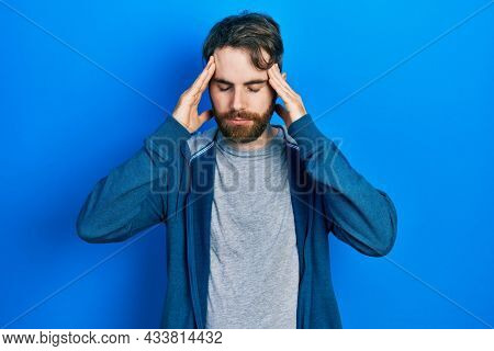 Caucasian man with beard wearing casual sweatshirt with hand on head for pain in head because stress. suffering migraine.