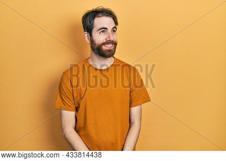 Caucasian man with beard wearing casual yellow t shirt smiling looking to the side and staring away thinking.